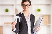 stock photo of model home  - Happy realtor woman is holding model of home looking at the camera and smiling - JPG