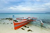 stock photo of camiguin  - traditional filipino banka outrigger fishing boat on white sand beach of camiguin island near mindanao in the philippines - JPG