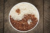 image of rice  - Brown rice and white rice in cup have wood table is backgruond.