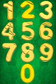 image of zero  - The numbers one till nine and followed by a zero in golden yellow colour on a green velvety background - JPG