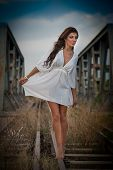 image of cross-dress  - Sensual girl with white dress walking on the railway under the blue sky - JPG