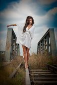 picture of cross-dress  - Sensual girl with white dress walking on the railway under the blue sky - JPG