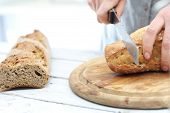 image of hand cut  - Woman hands cutting bread on the kitchen counter  - JPG
