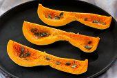 stock photo of butternut  - Cut butternut squash with pumpkin seeds on black tray horizontal - JPG