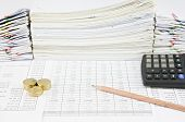 picture of piles  - Brown pencil and pile of gold coins with calculator on finance account have pile of paperwork as background - JPG