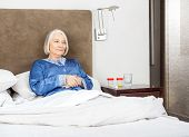 image of thoughtfulness  - Thoughtful senior woman relaxing on bed at nursing home - JPG