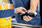 picture of card-making  - Cropped image of man making payment through smartphone using NFC technology at cinema - JPG