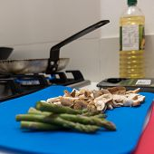 picture of spears  - Healthy fresh asparagus spears and diced mushrooms on a colorful blue chopping board in a kitchen close to a frying pan heating on a gas hob ready to fry the vegetables focus to the mushrooms - JPG