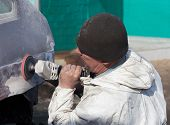 stock photo of putty  - Worker performs repairing car body leveling putty before painting - JPG