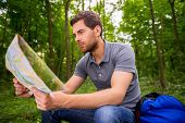 picture of concentration man  - Concentrated young man with examining map while sitting in a forest with backpack laying near him  - JPG