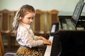 foto of grand piano  - Cute little girl playing grand piano in music school childhood concept - JPG