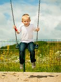 picture of swings  - Little blonde boy having fun at the playground. Child kid playing on a swing outdoor. Happy active childhood.