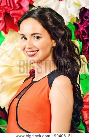 Pretty brunette woman looking at camera and smiling. Floral background.