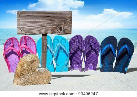 Wooden Heart And Flip Flops On Beach