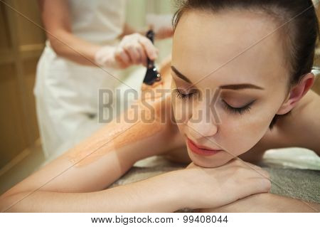 Relaxed Woman Having Clay Body Mask Apply By Beautician