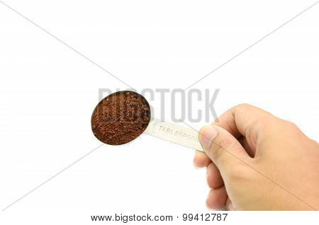 hand holding table spoon with ground coffee in white background