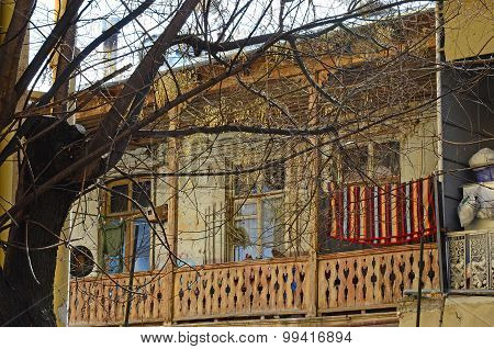 Old wooden balcony with a bright mat on the rope. Tbilisi, Georgia
