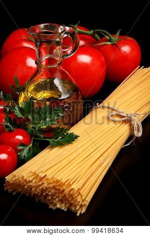 Pasta Raw Isolated On Black With Tomatoes,olive Oil,garlic Verti