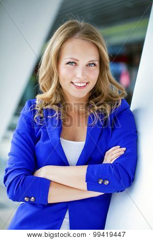 Beautiful young blonde in a blue jacket, portrait outdoors