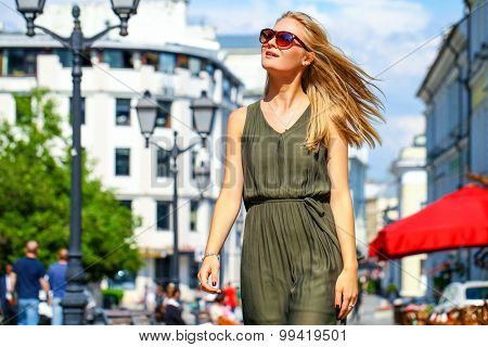 Close up, attractive young blonde woman in long dress walking in summer street