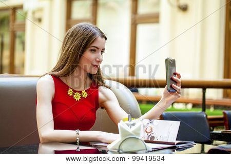 Selfie, Young beautiful girl photographed on a cell phone in coffee shop