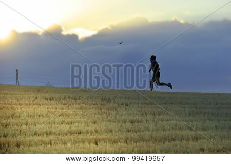 Profile Silhouette Of Young Man Running In Countryside Practicing cross country discipline On Sunset