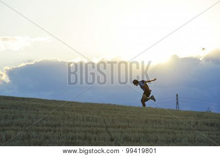 Profile Silhouette Of Young Man Running In Countryside Practicing Final Sprint On Sunset