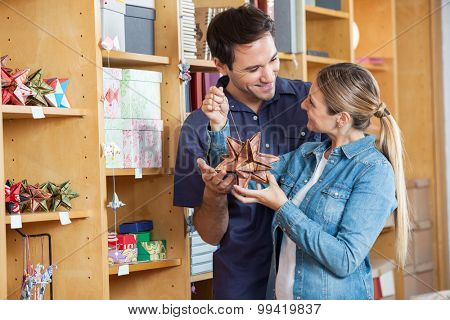 Mid adult couple smiling while holding at star shape decoration in shop