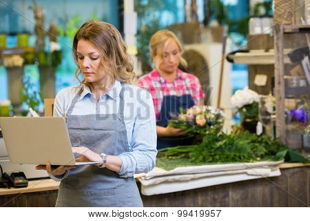 Female florist using laptop with colleague in background at flower shop