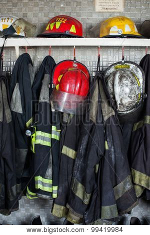 Firefighter suits and helmets arranged on shelf at fire station