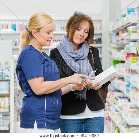 Mature female chemist explaining product details to customer in pharmacy