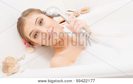 Young happy woman singing in bath
