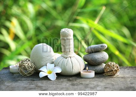Spa still life on wooden surface over green reeds background