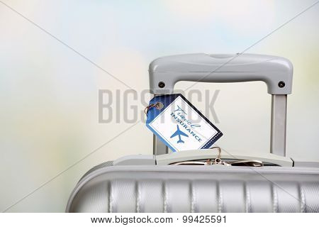Suitcase with TRAVEL INSURANCE label on light blurred background
