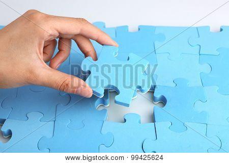 Female hand placing last piece of puzzle, closeup