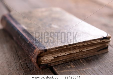 Old book on wooden table close up