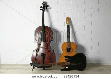 Musical instruments on white brick wall background