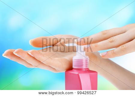 Female hands with cream on colorful blurred background