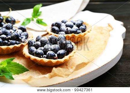 Delicious crispy tarts with black currants on parchment on wooden board, closeup