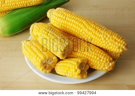 Fresh corn on cobs in plate on wooden table, closeup