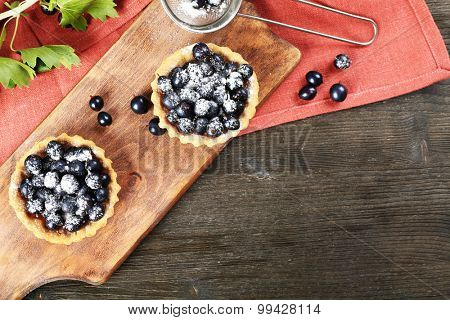 Delicious crispy tarts with black currants on wooden cutting board, top view