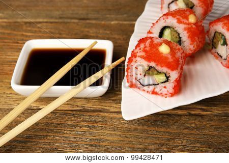 Rolls with sauce and sticks on wooden table close up