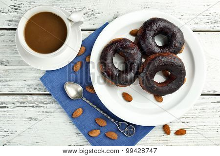 Delicious doughnuts with chocolate icing and cup of coffee on table close up
