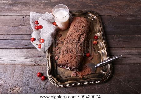 Chocolate roll with glass of milk on table close up