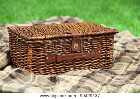 Wicker picnic basket  and plaid on green grass, outdoors