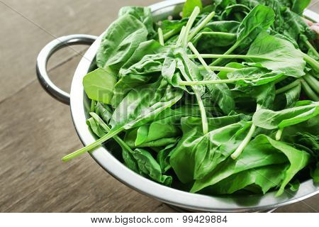 Fresh spinach leaves in colander on wooden table, closeup