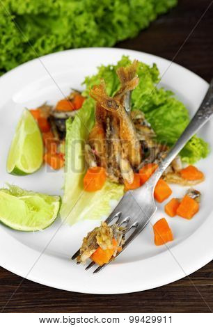 Fried small fish with carrot and greens on table close up