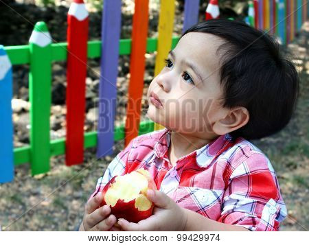 Baby boy eats apple on a children playground