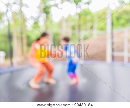 Blur Image Of Kid Jumping In Trampoline.
