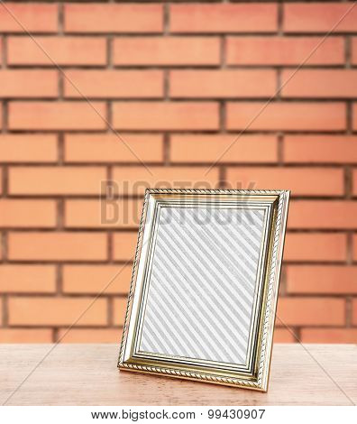 Old frame standing on table on brick wall background